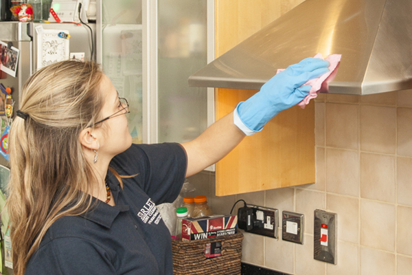 Cleaner wiping a kitchen for domestic cleaning London