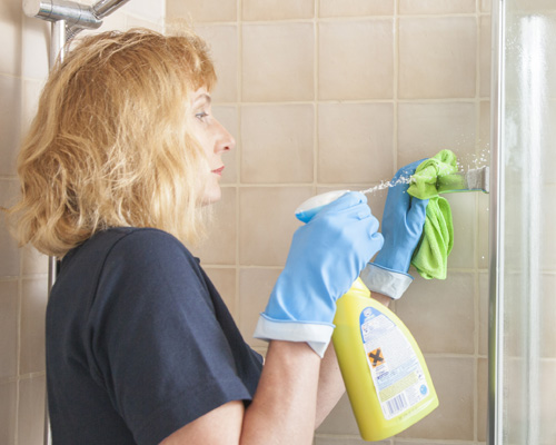 Worker cleaning a shower for Housekeeper London service
