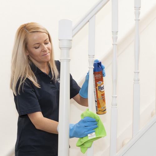Cleaner polishing a stairs banister for Spring Cleaning London