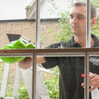Starlet cleaner carrying out window cleaning in London
